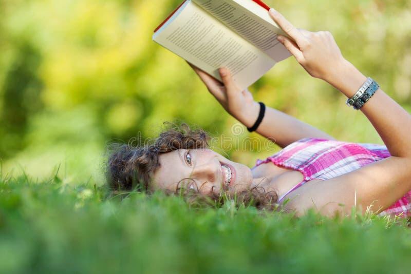 Le flickan med boken, medan ligga på gräs royaltyfria bilder