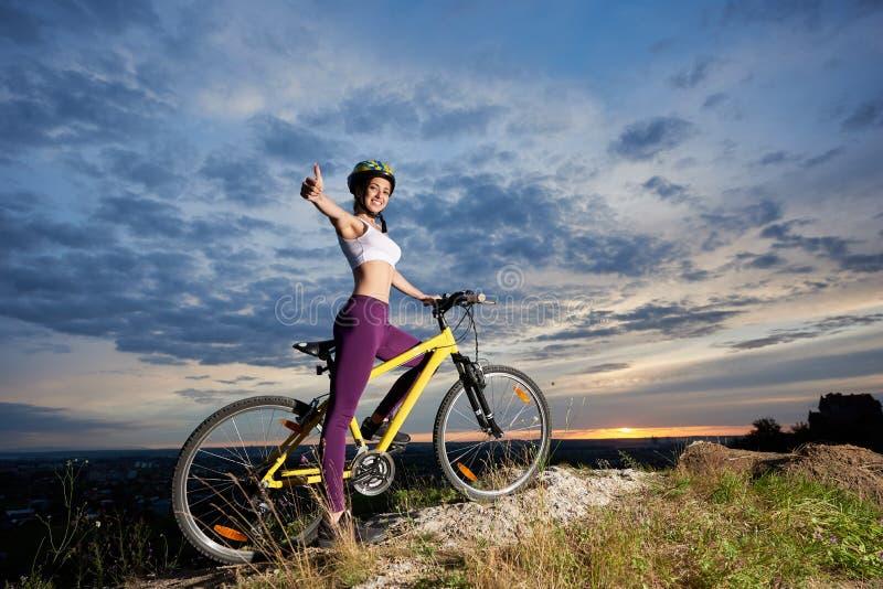 Le flickan med cykeln som ler upp och visar tummen arkivbilder