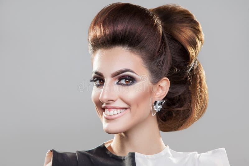 Le flickan med den trevliga eleganta frisyren som ser kameran royaltyfri fotografi