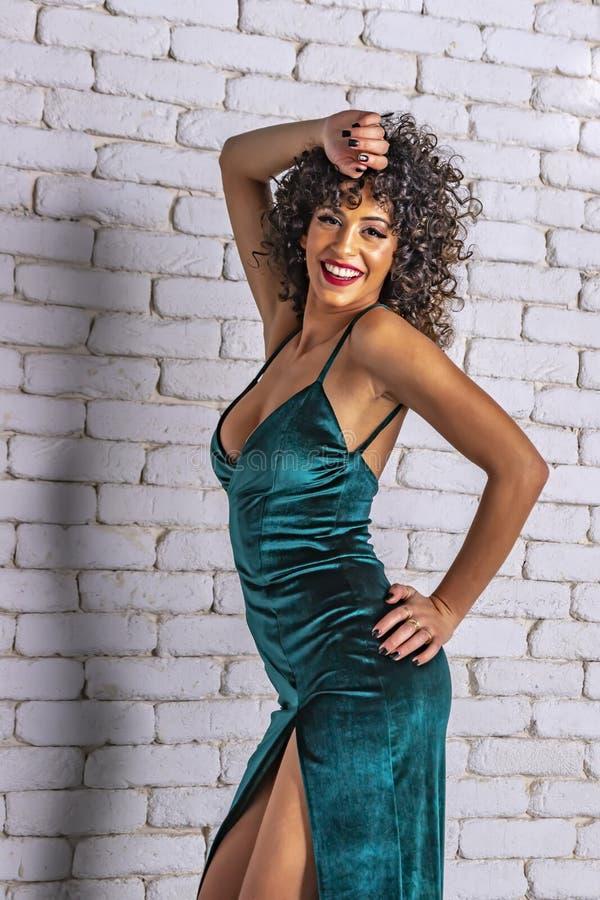 Le flickan med långt svart lockigt hår och makeup i en grön aftonklänning på en bakgrund av den vita tegelstenväggen royaltyfria foton