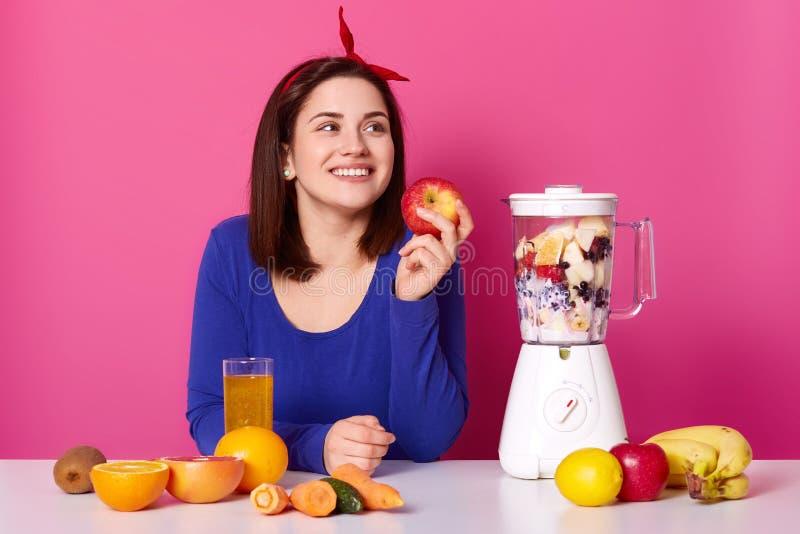 Le flickan med nya frukter på tabellen som isoleras över rosa bakgrund Damen ser åt sidan, medan göra coktail Kvinnan rymmer äppl royaltyfria foton