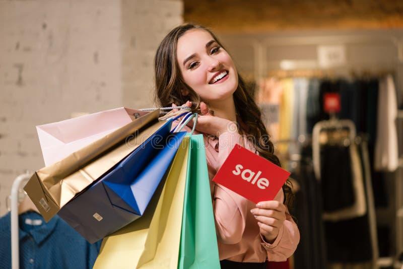 Le flickan med shoppingpåsar och försäljningstecknet royaltyfria bilder