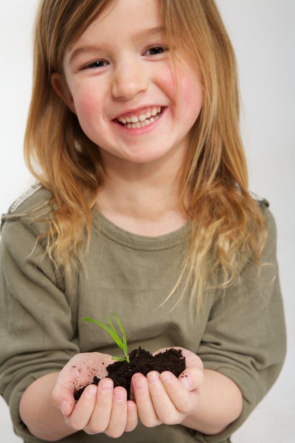 Le flickan med växten som växer från jord i händer royaltyfria bilder