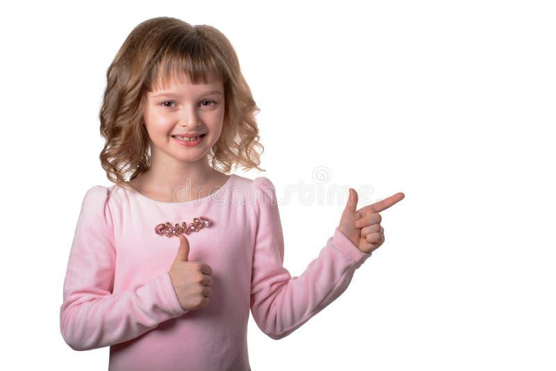 Le flickan som bort pekar fingrar på kopieringsutrymme som isoleras över vit bakgrund royaltyfri foto