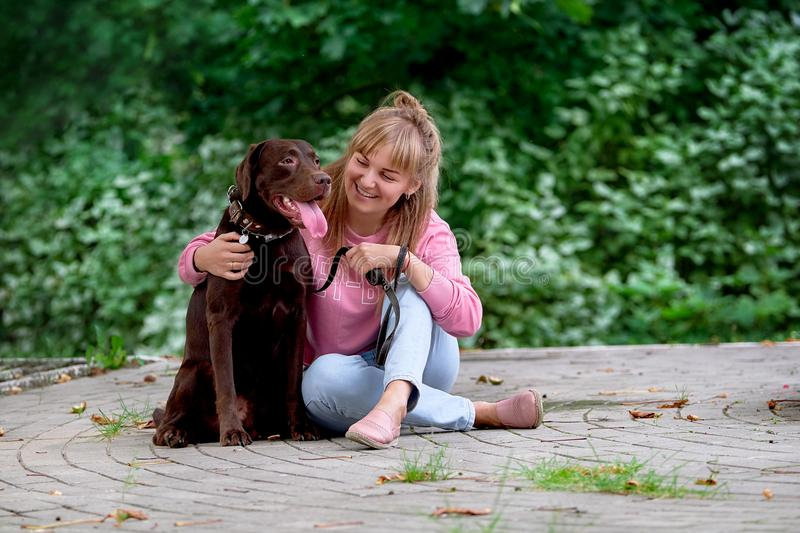 Le flickan som kopplar av med hunden Labrador som därefter sitter fotografering för bildbyråer