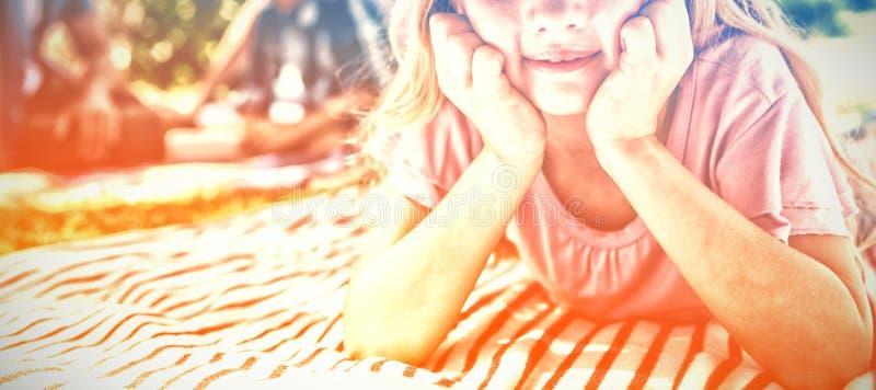 Le flickan som ligger på filten medan familjsammanträde i bakgrund royaltyfri fotografi
