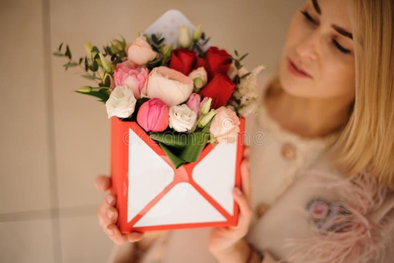 Le flickan som lite rymmer asken av mjuka röda blommor för rosa färger och för passion arkivbilder