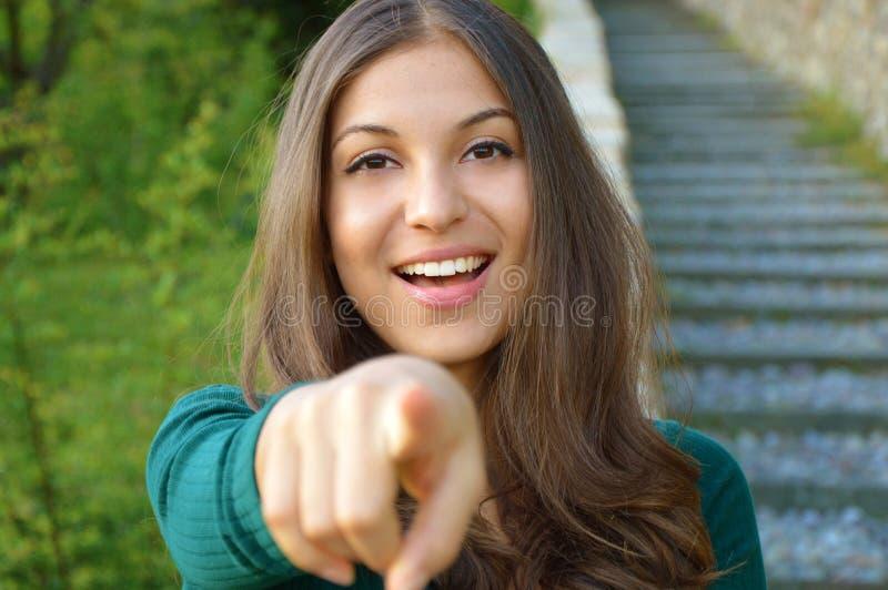 Le flickan som pekar fingret på kameran och det toothy leendet, fokus på hennes framsida arkivbilder