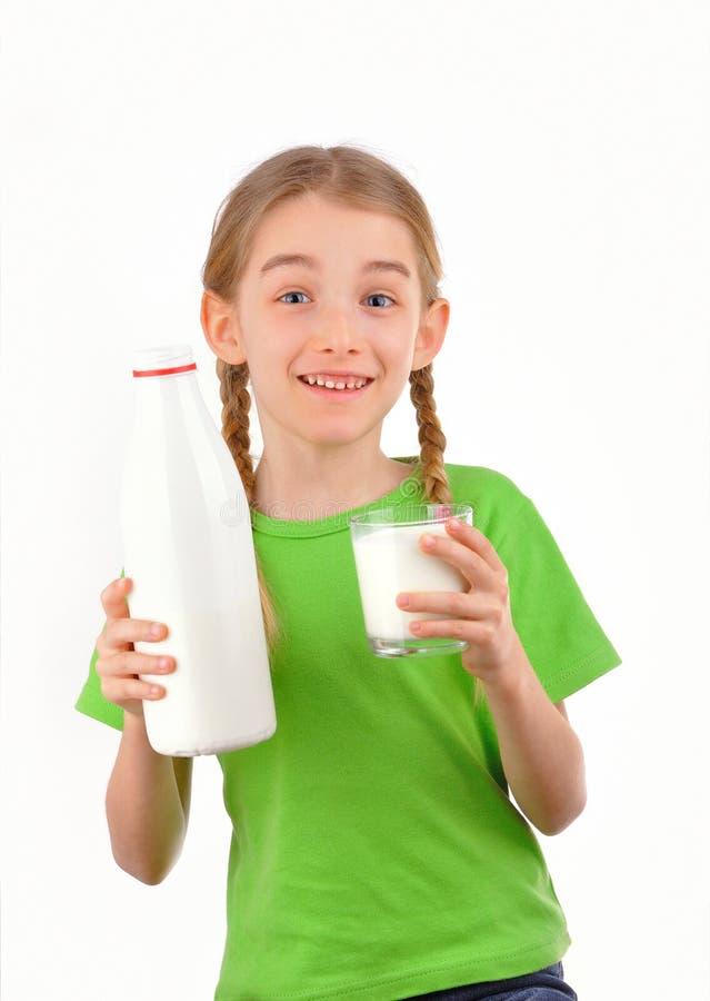 Le flickan som rymmer en flaska och ett exponeringsglas av, mjölka royaltyfri foto