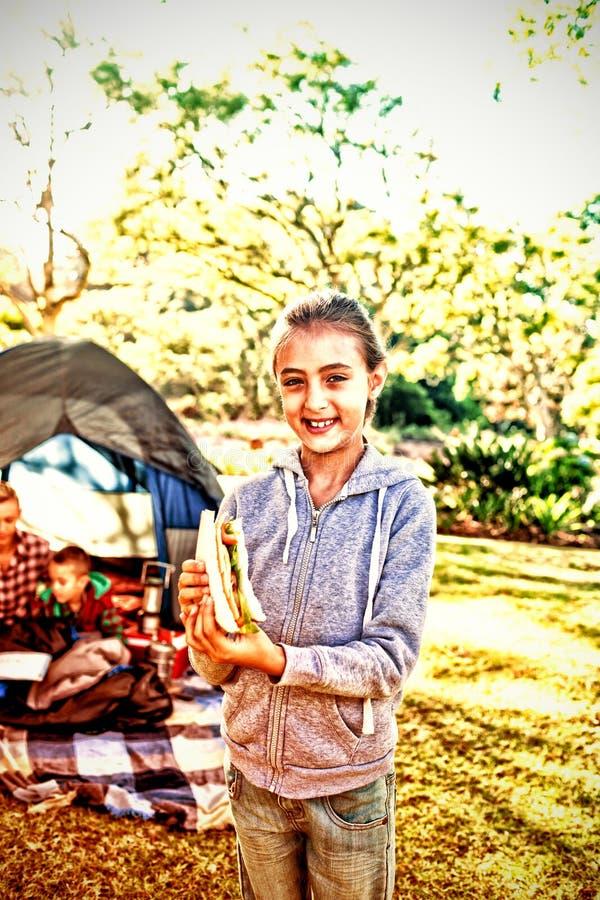 Le flickan som rymmer en smörgås på campingplatsen arkivbilder