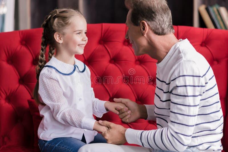 Le flickan som vilar med hennes farfar fotografering för bildbyråer