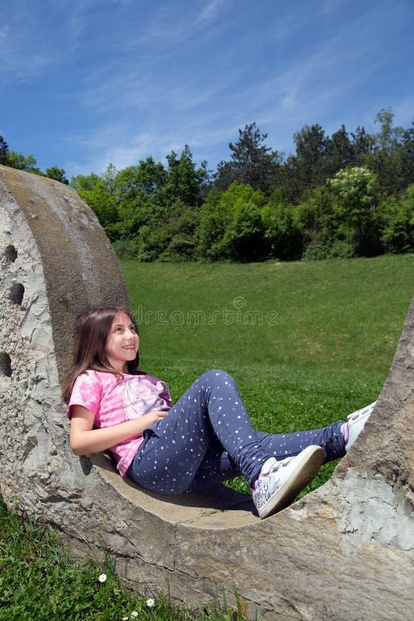 Le flickan som vilar på Stonewall och dagdrömmer i parkera på Sunny Spring Day arkivbild