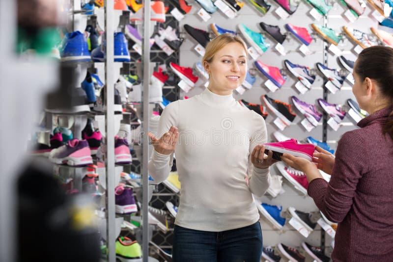 Le flickasäljaren som hjälper en kund i skoavdelning arkivbild