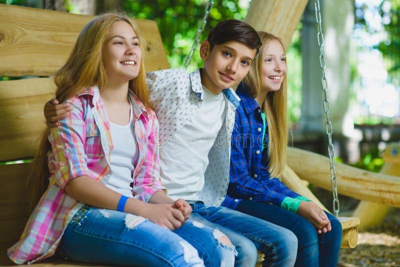 Le flickor och pojken som har gyckel på lekplatsen Barn som utomhus spelar i sommar Tonåringar på en gunga arkivbild