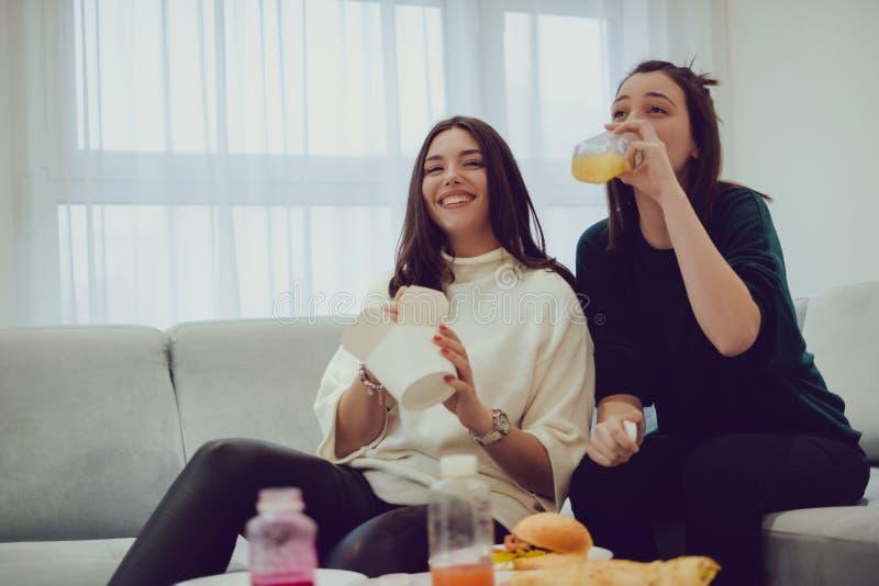 Le flickor som äter mat i vardagsrummet royaltyfria foton