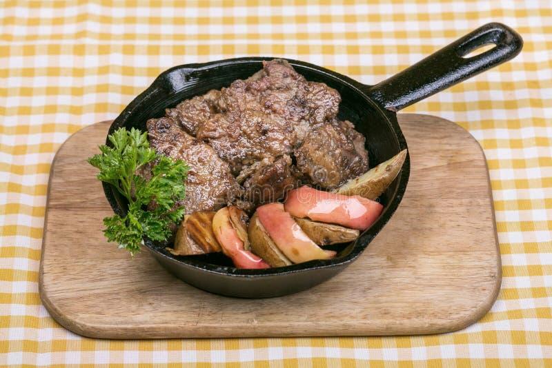 Le foie de poulet pané avec la pomme a servi dans une poêle, décorée des tranches de pommes et d'un brin de persil photographie stock