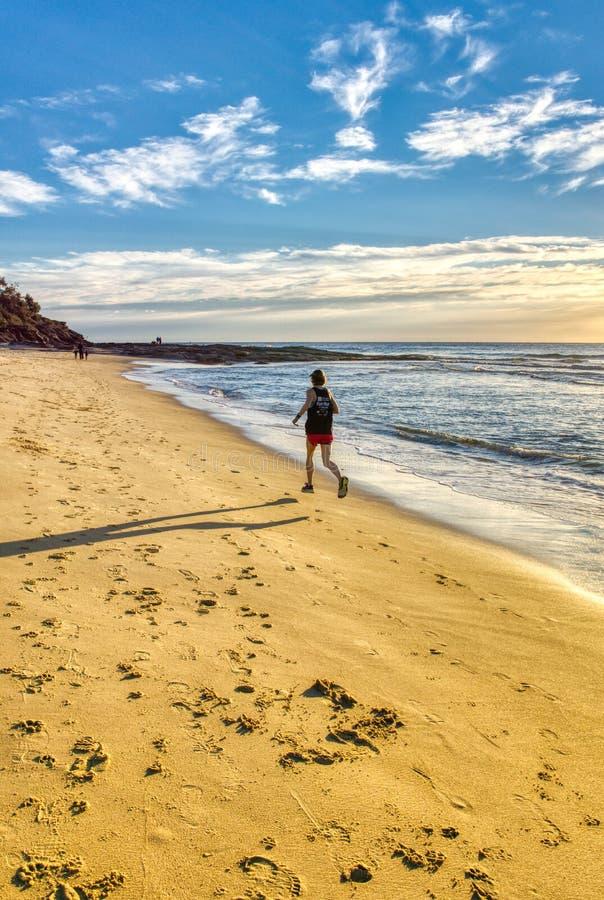 Le fonctionnement d'homme dans la plage aux wave's mous ciel bleu lumineux, copies d'aube de pied tracent en sable image stock