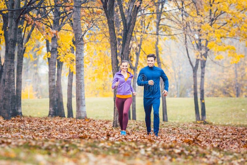 Le fonctionnement d'homme et de femme comme forme physique folâtrent en parc d'automne photographie stock libre de droits