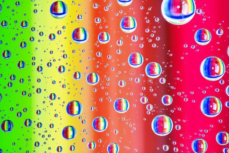 Le fond abstrait coloré de l'eau chute sur le verre avec des couleurs d'arc-en-ciel photographie stock libre de droits