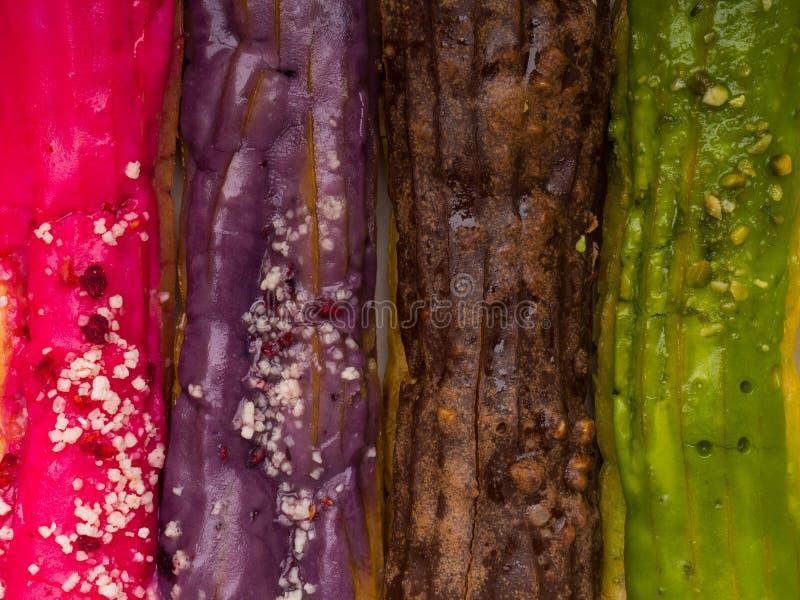 Le fond coloré d'eclairs, dentellent avec la baie, verdissent avec les pistaches, le chocolat, et la couleur pourpre image stock