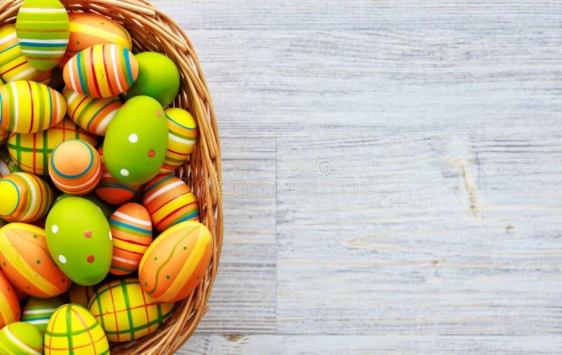 le fond a coloré le vecteur rouge de tulipe de format des oeufs de pâques eps8 oeufs colorés dans le panier sur le fond en bois photos stock
