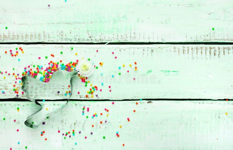 Le fond conceptuel de Pâques avec l'oiseau de coupeur de biscuit, fleurissent image stock