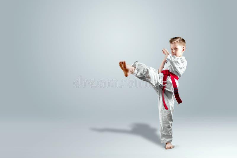 Le fond créatif, un enfant dans un kimono blanc fait un coup-de-pied, sur un fond clair Le concept des arts martiaux, karaté image stock