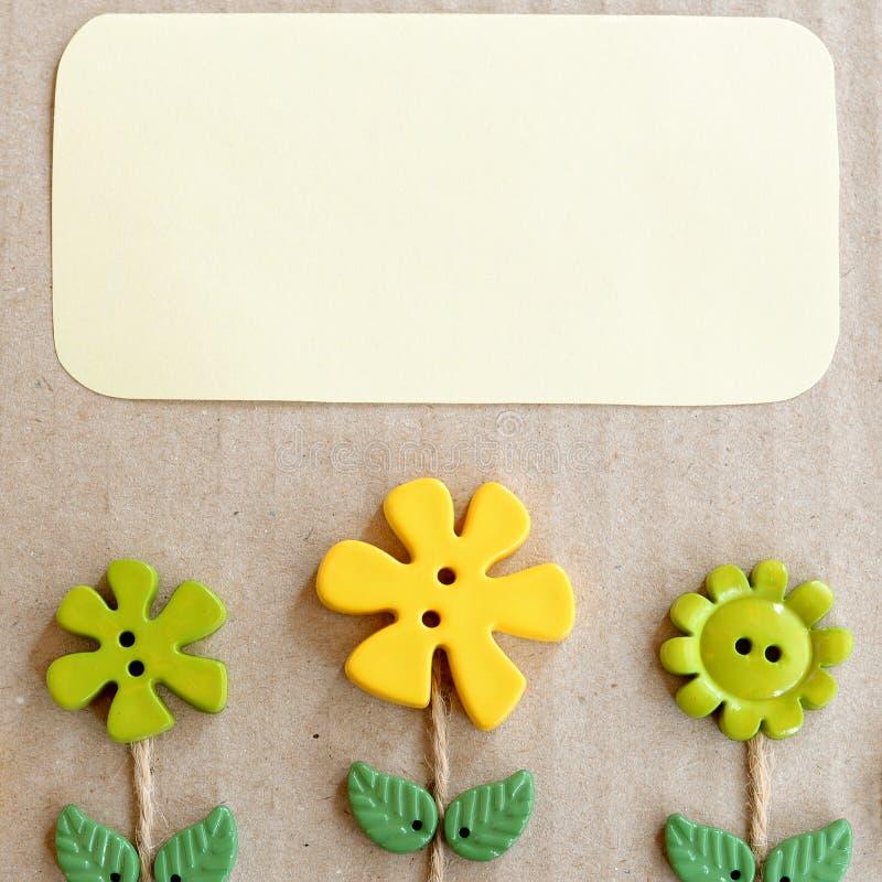 Le fond de carton avec du plastique vert et jaune boutonne des fleurs et des feuilles et l'espace vide de copie pour le texte Fon photos stock