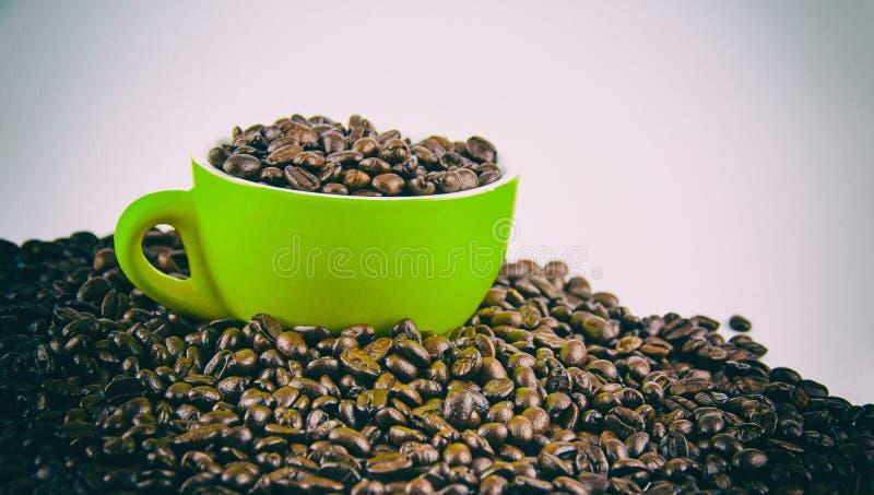 Le fond de conception d'art abstrait des grains de café rôtis et de la tasse en céramique, vieux style classique de film, ton lég photographie stock