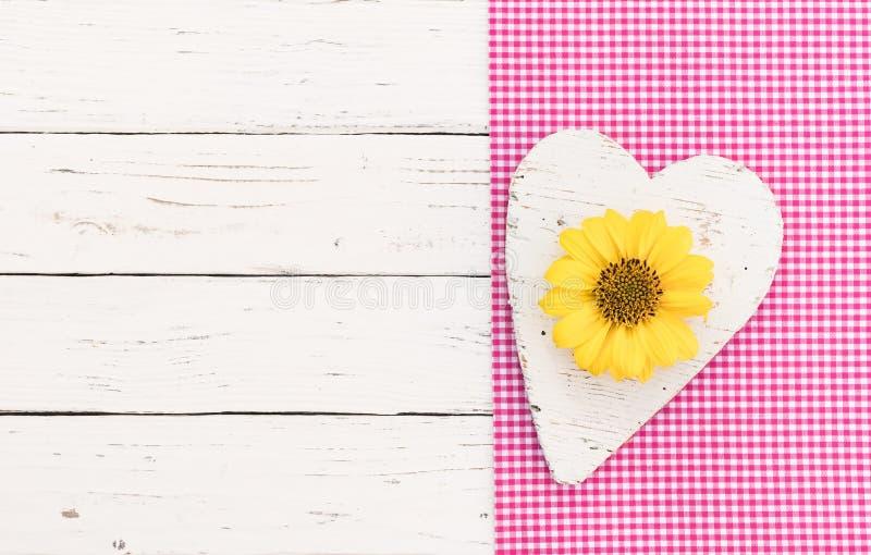 Le fond de jour de valentines ou de mères avec le coeur et la fleur se développent sur la frontière rose de tissu et le bois blan images libres de droits