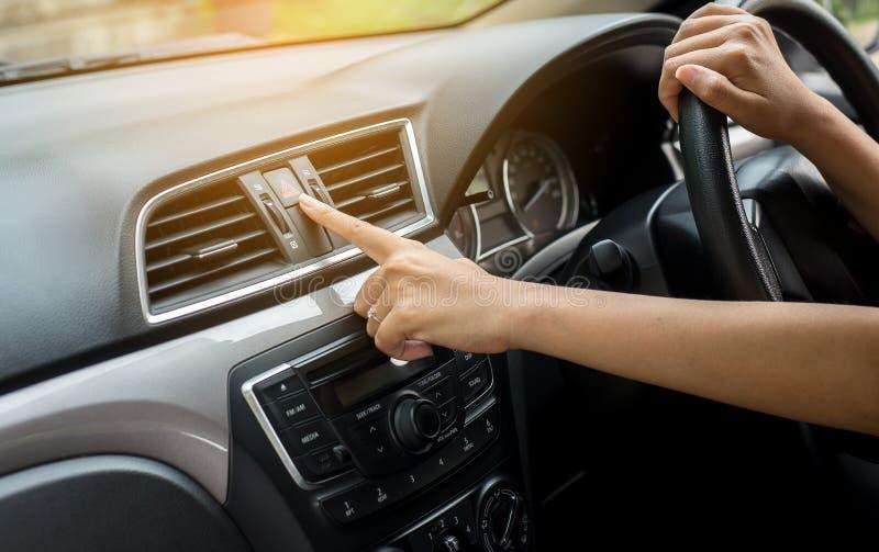 Le fond de lumière de secours de voiture de presse de conducteur de femme de main ou de doigt sur le tableau de bord photo libre de droits