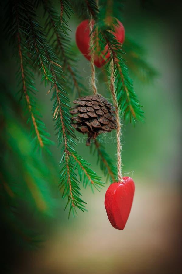 Le fond de Noël avec le cône de sapin et le coeur sur le sapin s'embranchent image libre de droits
