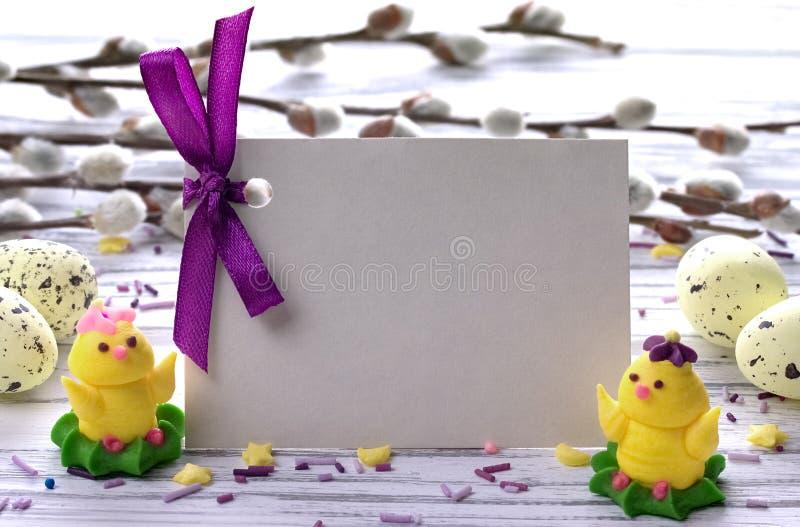 Le fond de Pâques avec le saule de chat jaune d'oeufs de pâques s'embranche ruban pourpre et petit espace de poulets pour le text photo libre de droits