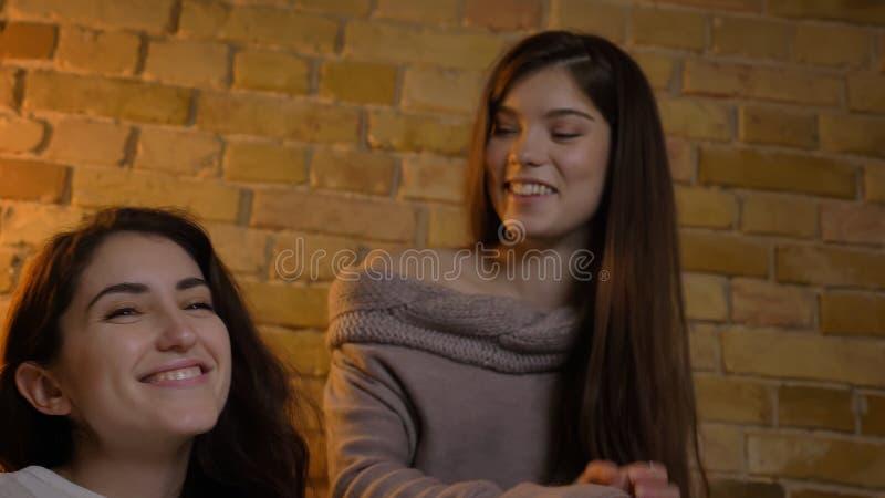 Le fond de plan rapproché vers le haut du portrait de deux jeunes jolies femmes regardant la TV rire heureusement dans un apparte photo libre de droits