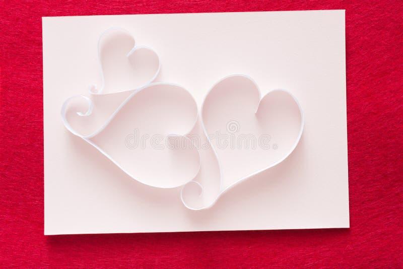 Le fond de Valentine avec le coeur de papier fait main forme la décoration sur la merde blanche du papier sur le feutre de rouge photos libres de droits