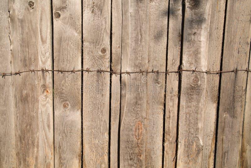 Le fond des panneaux gris de barrière avec des noeuds a martelé le barbelé en métal photos stock