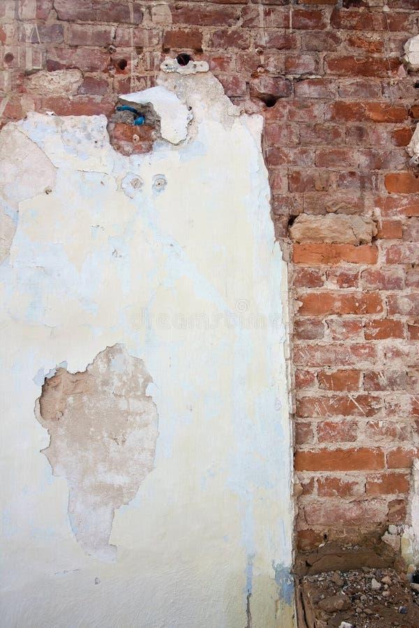 Le fond du plâtre criqué a couvert le vieux mur de briques minable, texture extérieure abstraite approximative verticale photographie stock libre de droits