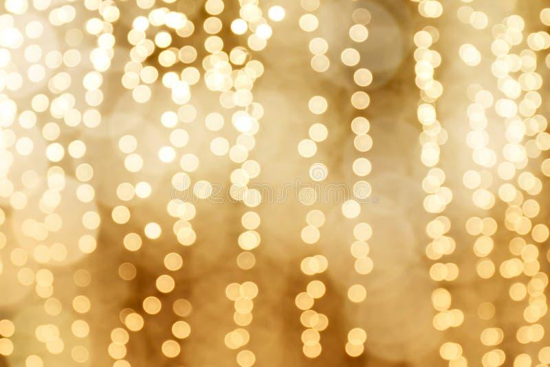 Le fond lumineux de bonne année de Noël d'or de bokeh d'éclairage, fond de couleur d'or de charme, a brouillé la lumière de nuit  photographie stock libre de droits