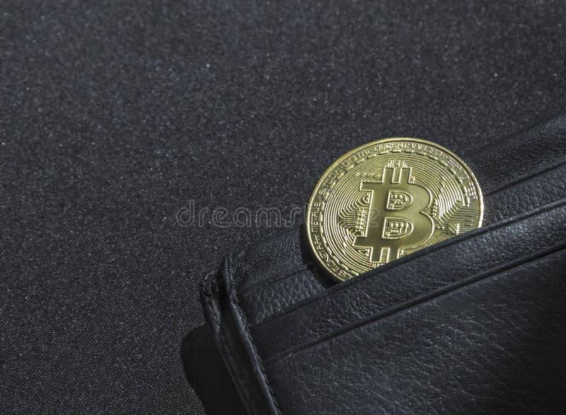 Le fond noir avec un bokeh avec des paillettes est une bourse en cuir noire de portefeuille pour l'argent avec un crypto bitcoin  photo stock