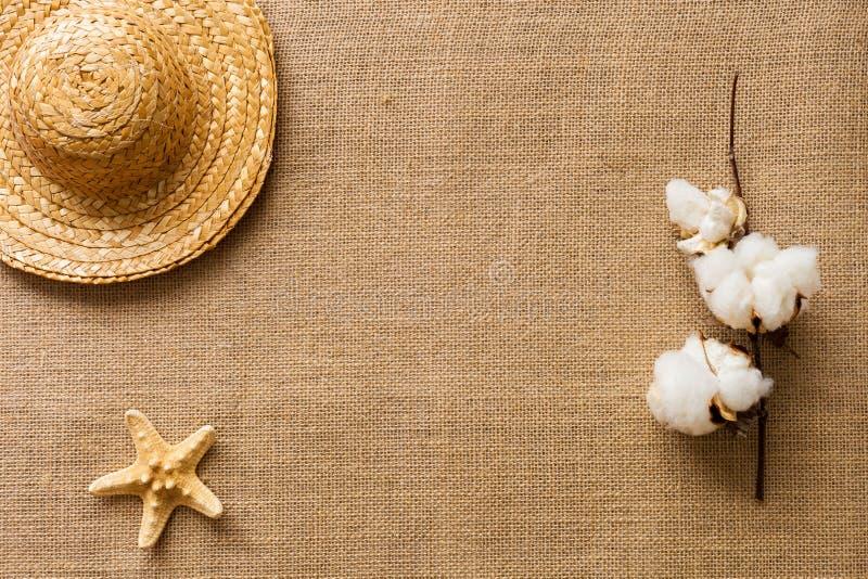 Le fond plat de configuration avec des étoiles de mer, le chapeau de paille et le coton fleurissent sur le tissu de toile de jute photographie stock