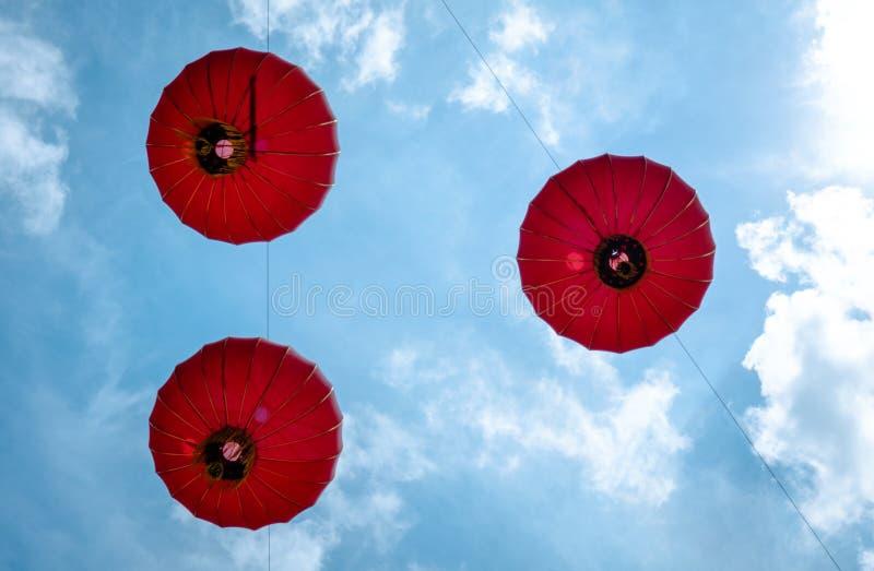 Le fond vers le haut du point de vue à accrocher rouge de lanterne haut en ciel bleu image stock