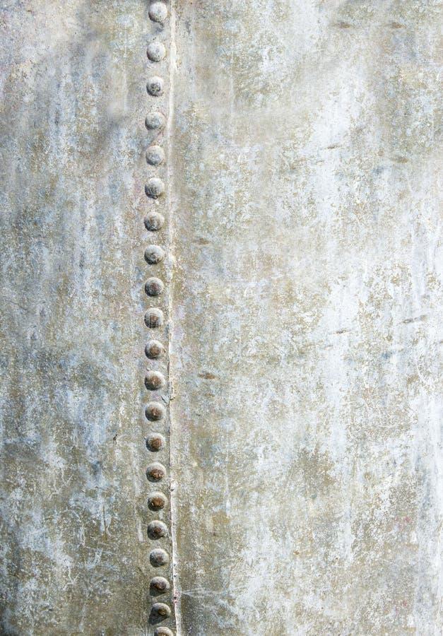 Le fond vide vertical du métal avec des rivets avalent un côté image stock