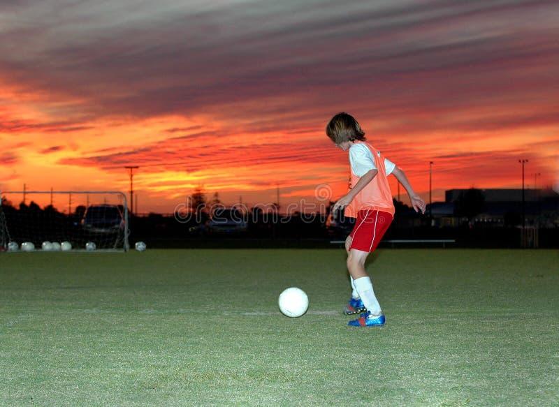 Le football au coucher du soleil photographie stock