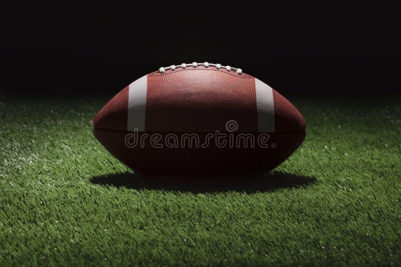 Le football d'université sur le champ d'herbe la nuit avec l'éclairage de tache photo stock