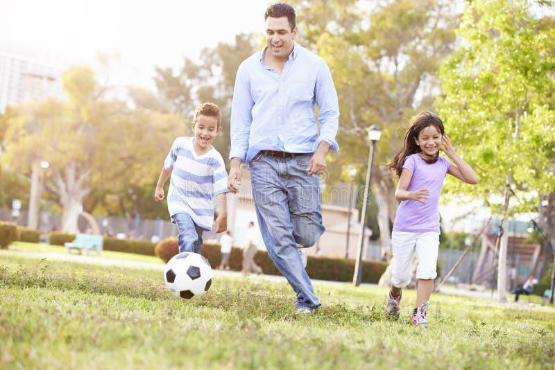 Le football de With Children Playing de père en parc ensemble images stock