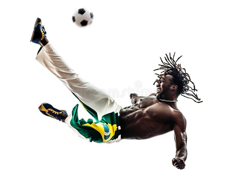 Le football de coup de pied de footballeur brésilien d'homme de couleur photographie stock libre de droits