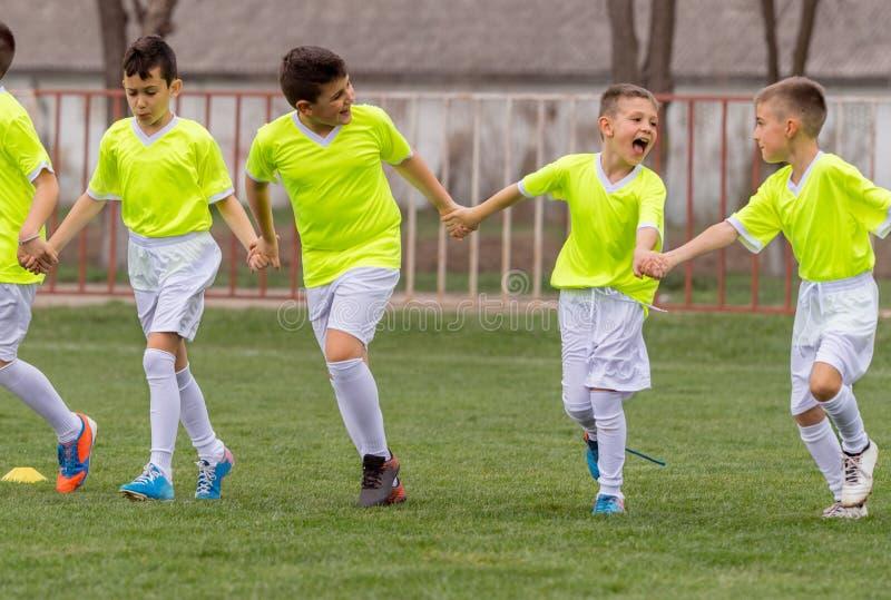 Le football de joueurs d'enfants en bas âge tenant des mains sur le champ image stock