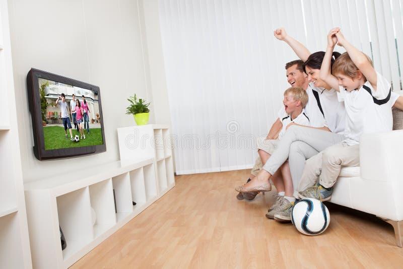 Le football de observation de jeune famille photographie stock libre de droits