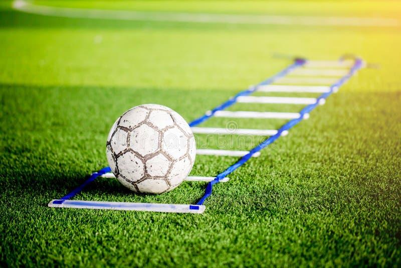 Le football entre les exercices d'échelle sur le gazon artificiel vert le pied images stock