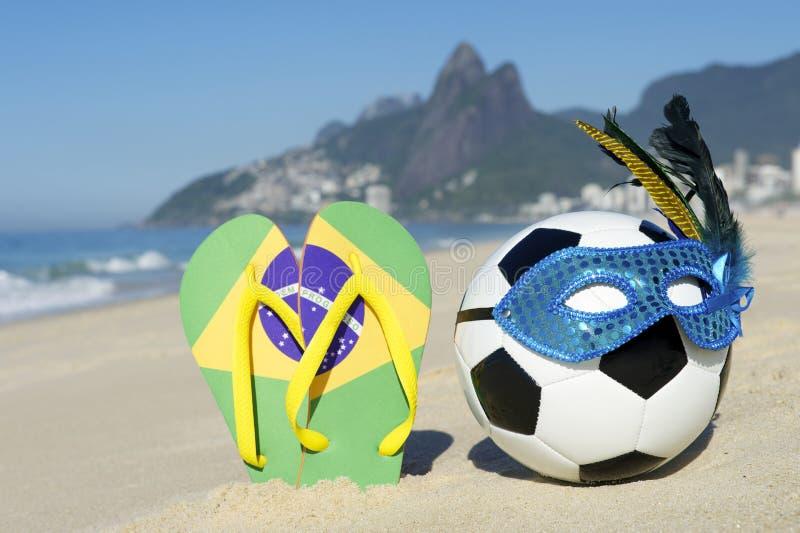 Le football et Flip Flops de ballon de football de masque de carnaval sur la plage Brésil photographie stock libre de droits